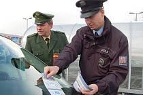 Policista Václav Suttner se svým německým kolegou Andreasem Pfortem dávají za stěrač jednoho z vozů na parkovišti Globusu varování před zloději.