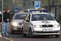 Kadaňští strážníci i státní policisté vyjíždějí z areálu prunéřovské elektrárny, v autě mají naložené aktivisty Greenpeace.