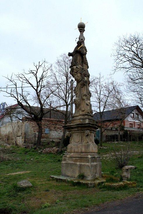 Na návsi v obci Škrle najdete kostelík a na sloupku posezení kešku.