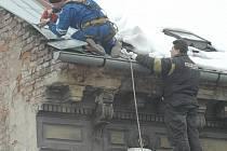 Řemeslníci strhli část oplechování na štítové zdi, vynosili narušené cihly a maltu a s pomocí nemrznoucí směsi vystavěli chybějící část střechy.