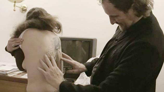 Přemysl Rabas si prohlíží tetování dominy, které vystupovala v dokumentu Nebe, peklo.