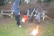 Muži kolem ohniště v parčíku.