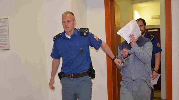 Obžalovaný Pavel Jaroš si cestou do soudní síně ukrývá tvář před objektivy fotoaparátů novinářů.