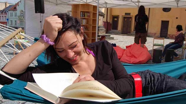 Petra Ungerová si čte ve venkovní knihovně.