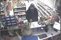 Lupič s pistolí v ruce, jak ho zachytila kamera uvnitř benzinky.
