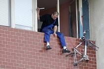 Muž sedí na balkoně v desátém patře. Chtěl skočit dolů.