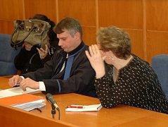Kabelkou si obličej zakrývá Jaroslava Lochařová, ke svému obhájci se naklání Šárka Hatašová. Obě se už třetím rokem zpovídají z týrání svěřené osoby před chomutovským soudem.