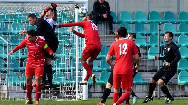 Na snímku jedna z šancí Chomutova (černí). Ve výskoku v souboji o míč Vojtěch Kubíka a gólman Štětí Václav Sailer.