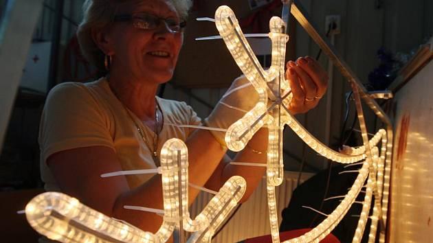 """""""Já prostě Vánoce zbožňuju,"""" rozplývala se šéfka party montážních pracovnic Kateřina Čermáková. """"Mám doma všechno možné, girlandy, světla na balkóně. Na snímku potahuje konstrukci oblíbené vánoční výzdoby ve městech světelným kabelem."""