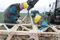 Energetici plzeňské společnosti instalují na polích u Hrušovan na Chomutovsku provizorní stožáry vysokého napětí poté co vlivem silného náporového větru došlo k deformaci a pádu dvou stávajících stožárů.