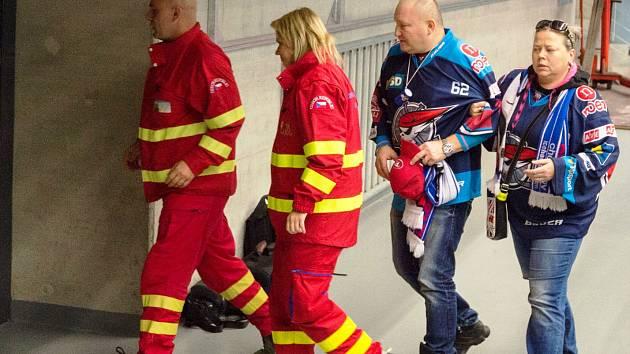 Záchranáři jdou s fanouškem k sanitce, ještě netuší, že se za několik chvil rozpoutá boj o jeho život.