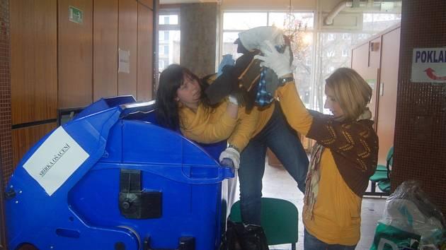 LIDÉ plní připravené kontejnery nepotřebným oblečením.