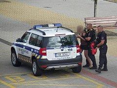Strážníci vedou ženu do služebního vozu