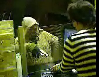 Fotografie z kamerového záznamu - lupič s pistolí v ruce si bere peníze.