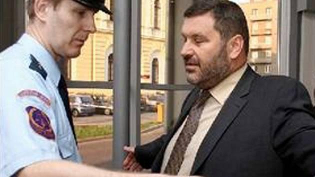 U SOUDU. Alexandra Nováka kontrouje justiční stráž při vstupu do soudní budovy. Jednání v březnu loňského roku bylo první a zatím jediné. Zmizel totiž hlavní svědek – Peter Schmel.