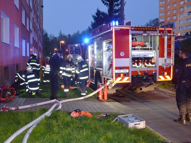 Hasiči a policisté u vchodu paneláku v Krušnohorské ulici v Jirkově, odkud museli v pátek evakuovat čtyři desítky lidí.