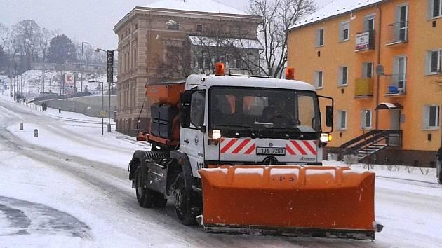 Sypač s pluhem při údržbě Mostecké ulice.