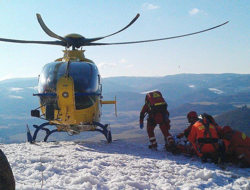 Hasiči vytáhli zraněného muže na kopec, kam přiletěla záchranářská helikoptéra.