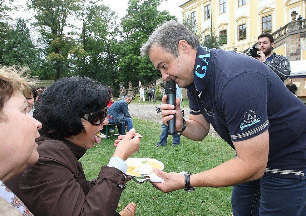 Moderátor akce Martin Zounar dává ochutnávat jednu ze soutěžních porcí i lidem v publiku.
