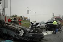 NEHODA. Mercedes po srážce skončil na střeše. Další dvě auta mají zdemolované přední části vozu. Nehoda si naštěstí vyžádala jen lehké zranění.