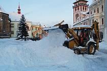 Technika stahuje sníh  z celého náměstí na jednu hromadu.