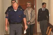 Eskorta přivádí obžalovaného do jednací místnosti chomutovského soudu. Se žádostí o propuštění z vazby neuspěl.