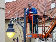 Pracovník technické správy instaluje vánoční výzdobu v ulicích Chomutova