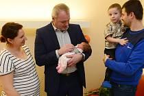 Ema Vojtěchová v náruči chomutovského primátora Marka Hrabáče. Přihlížejí maminka, tatínek a bráška Vojta.