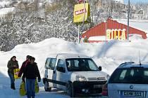 AZUROVÉ NEBE A HORY SNĚHU. Lidé je zdolávají i před vejprtským supermarketem. Chodníky na horách v těchto dnech neexistují. Na protažených silnicích se míjejí auta s pěšími.