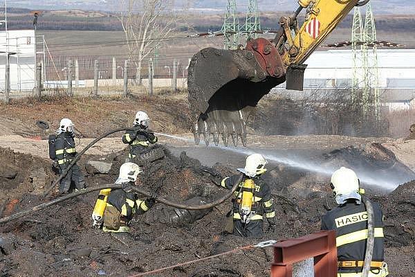 Bagr odkryje penumatiky zahrnuté jílem a hasiči je prolijí vodou.