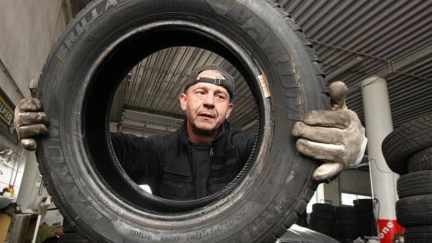 """Josef Drbohlav ve svém pneuservisu. """"Bereme lidi, jak přijedou,"""" říká."""