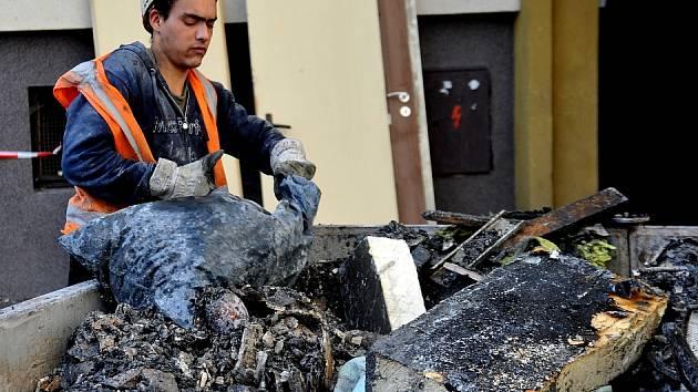 Dělníci vyklízejí dům, ve kterém vyhořelo několik bytů v podkroví.
