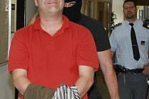 Poněkud křečovitý úsměv a bunda jakoby ležérně přehozená přes ruce. Má ale jiný účel – skrýt pouta na rukách. Pavel Karel Markvart před včerejším soudem, který rozhodl o jeho vazbě.