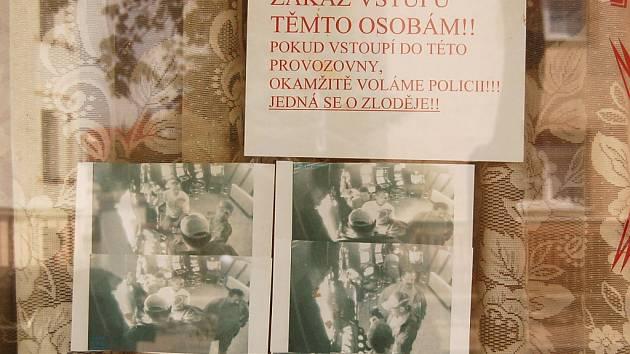 Takováto cedule s nápisem a fotografiemi z kamery visí na výloze restaurace.