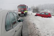 U Mikulovic na Klášterecku sjelo z kluzké vozovky celkem devět aut. Hasiči je postupně dostávali na silnici.
