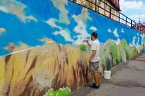 Grafik a designér David Jasný (na snímku), připravuje základní plochu výzdoby opěrné zdi v Pražské ulici. Až budou základy hotové, přijdou na řadu spreje, které dají malbě finální podobu.