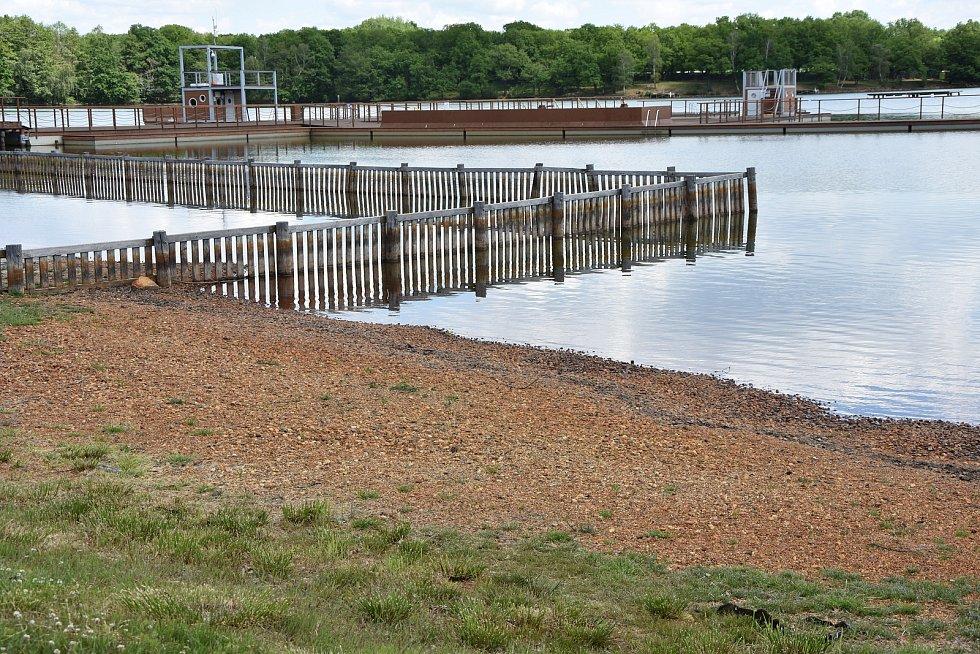 Klesající hladina odhalila kamenité břehy. Zakryje je 180 tun písku.
