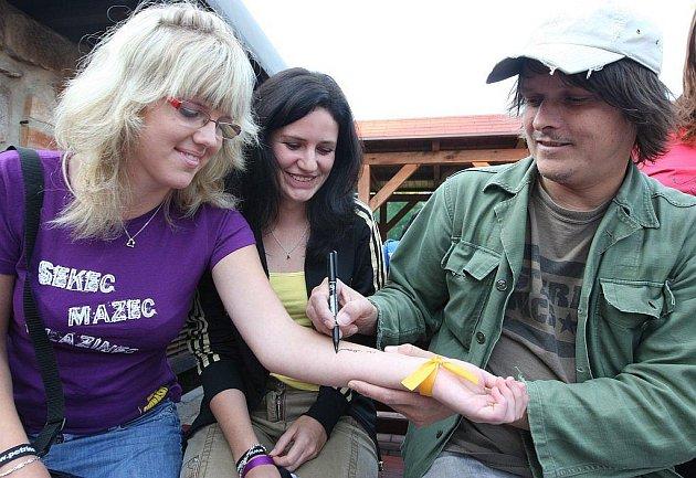 Zpěvák skupiny Chinaski Michal Malátný se podepisuje na ruku jedné z fanynek.