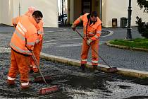 Pracovníci technické správy vmetají jemné kamínky do spár dlažby na chomutovském náměstí 1. máje.