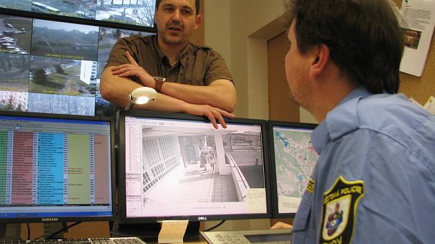 """Starosta Jirkova Radek Štejnar diskutuje se strážníkem obsluhujícím kamerový systém ve """"velíně"""" místní městské policie, zda se na stěnu vejdou další monitory od kamer sledujících Ervěnice."""