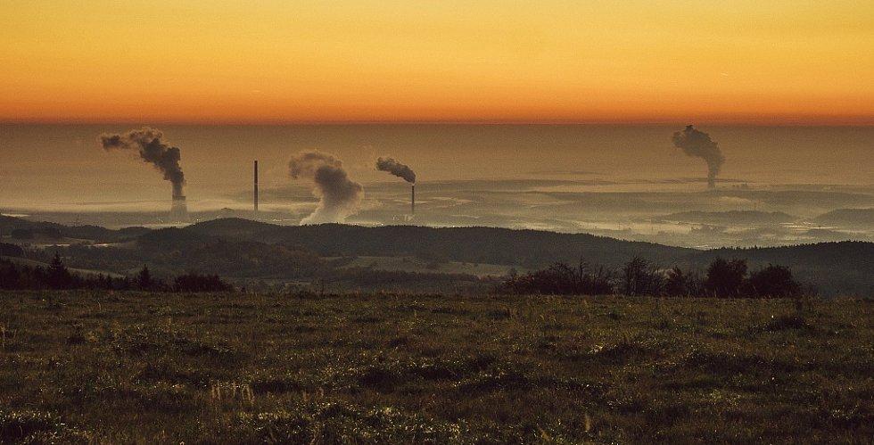 Pohled na severočeskou hnědouhelnou pánev s elektrárnami Prunéřov I, II a Tušimice v podzimním svítání doprovázeným mlhou v níže položených místech. Říjen 2017