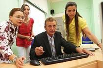 Ředitel chomutovského soukromého gymnázia Pavel Cibulka s učitelkami zkouší nový počítač.