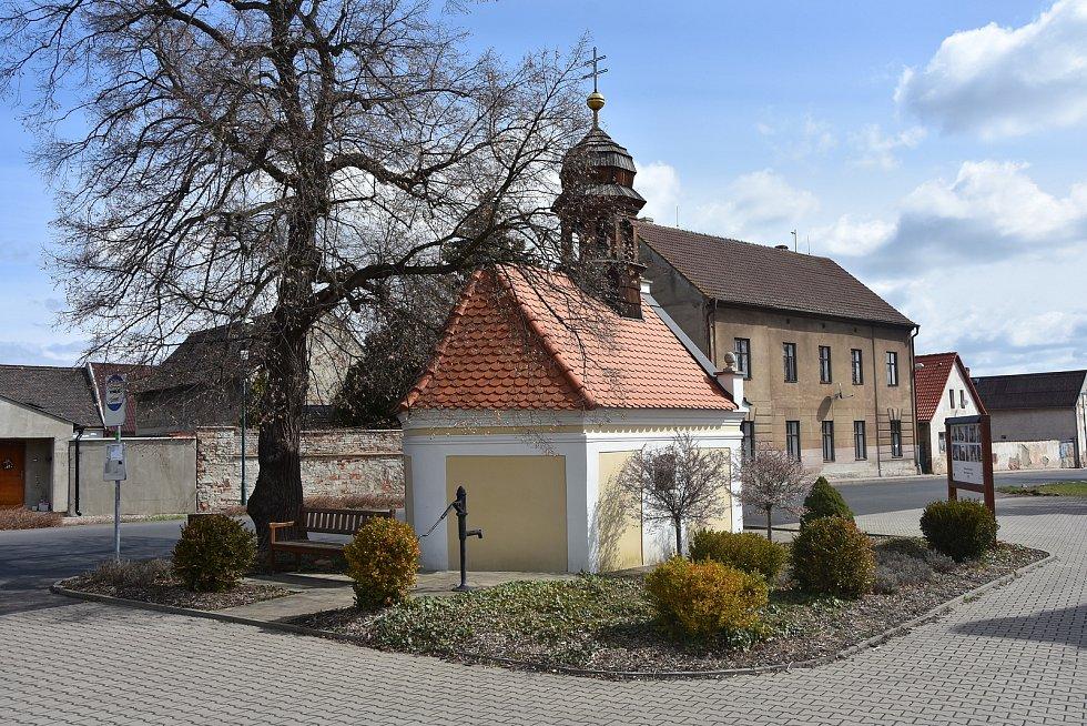 Na návsi v Hořenci stojí kaple sv. Anny. Za ní je autobusová zastávka s lavičkou.