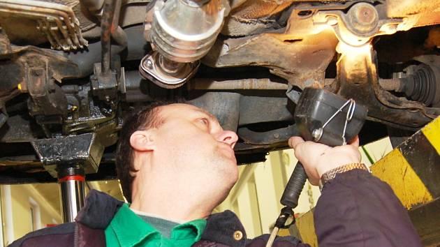 Technik prohlíží spodní část aut při kontrole.