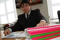 PŘEDSEDA soudu Petr Šustr za svým stolem a několik spisy, které se chystá kontrolovat. Mají barevné obaly, podle toho, jak jsou staré. Zelené jsou starší než pět let, čtyřleté jsou žluté a červené pak ty, které jsou starší než tři roky.