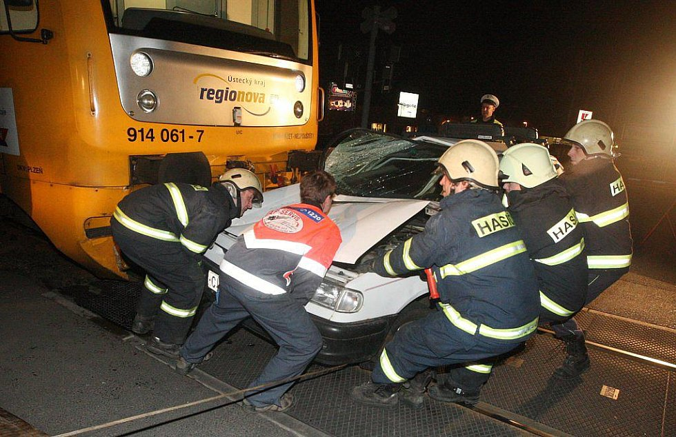 Hasiči odtahují rozstřihané auto zpod vlaku.