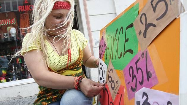 DVACET PĚT, PADESÁT NEBO SEDMDESÁT PĚT PROCENT SLEVA. Na snímku lepí papírky se slevami na tabuli majitelka etnického obchodu v Revoluční ulici Judita Naďalová.