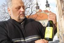 Karel Němeček s lahví svého vína.