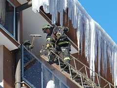 Na snímku jeden z vejprtských dobrovolných hasičů ze žebříku odstraňuje motorovou pilou zledovatělé rampouchy ze střechy domu. Pokud by se některý uvolnil, mohl by pádem na chodník ohrozit procházející chodce.