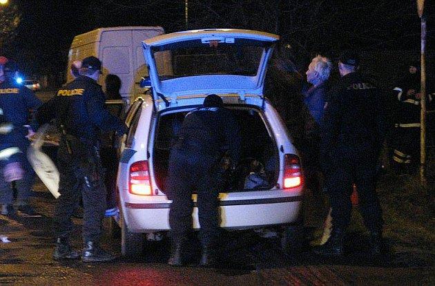 Policisté nakládají do auta několik zatčených. Podle svědků v domě vařili drogy.